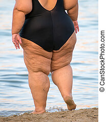 Overweight woman on the beach. Unrecognizable person.