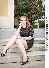 Overweight woman sitting dressed in