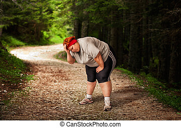 Overweight woman tired after a run in the forest. Burning of calories. Female obesity, bulimic. Unhealthy food eating