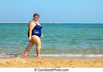 overweight woman walking on beach