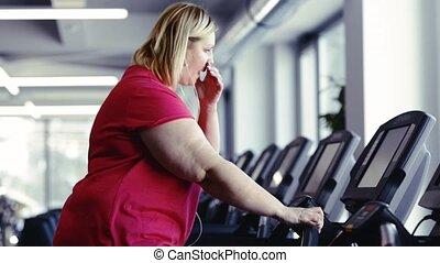 Overweight woman walking on treadmill in modern gym. -...