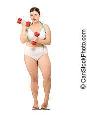 overweight woman with dumbbells on scales