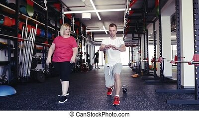 Attractive overweight woman with her personal trainer in pink t-shirt in modern gym working out, doing lunges. Chubby young blonde woman at fitness center.