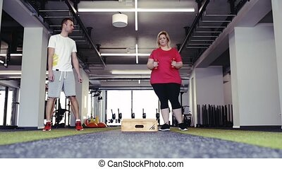 Overweight woman with personal trainer in modern gym working out.