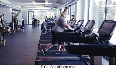Overweight woman with trainer walking on treadmill in gym.