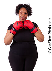 Overweight young black woman holding boxing gloves, isolated on white background - African people