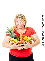 Overweight young woman with basket of fresh fruit