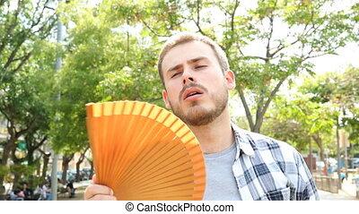 Overwhelmed man fanning suffering a heat stroke outdoors in...