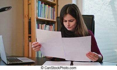 Overwhelmed woman with documents and laptop in home - Sad...