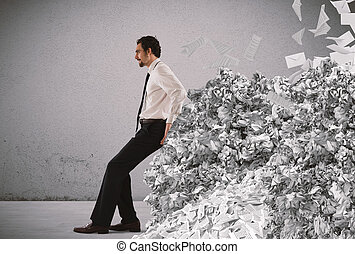 Overwork and spam - Businessman pushing with fatigue a big...