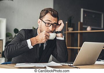 overworked businessman drinking coffee