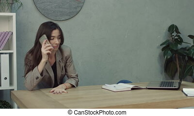 Overworked tired businesswoman awakened by phone call while taking a nap at her workplace with her feet on office desk. Exhausted female entrepreneur waking up by phone ring in office.