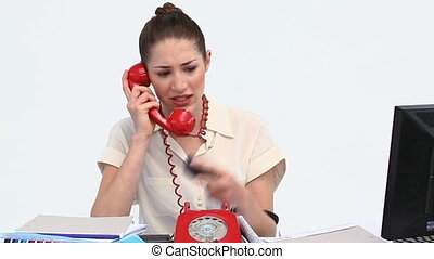 Overworked businesswoman picking up two phones against white background