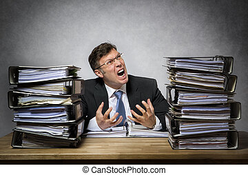 Overworked crying businessman with lot of files on his desk