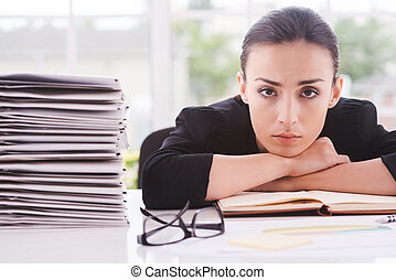 Overworked executive. Depressed young woman in formalwear looking at camera and leaning her face at the table with stack of documents laying near