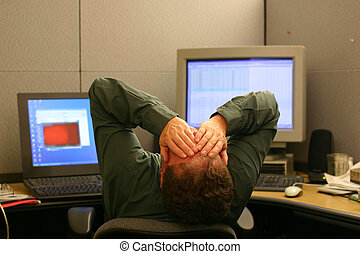 man leaning back in his cubicle with his hands over his face