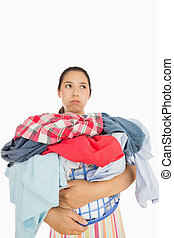 Overworked young woman holding basket full of dirty laundry