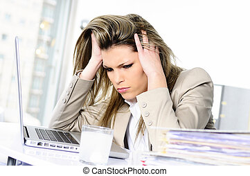 Overworked - young woman stressed at work, taking an aspirin...