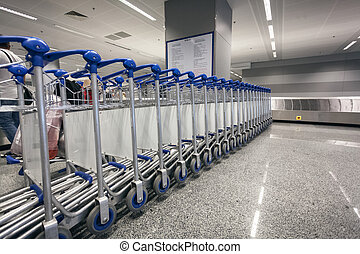 ow of luggage trolleys at airport terminal - Long row of...