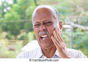 Closeup portrait elderly business man with tooth ache crown problem cavity grimacing from pain touching outside mouth with hand isolated outside background. Negative human emotion facial expression