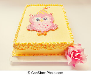 Yellow birthday cake with pink owl of sugar on the top.