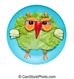 Owl made of fresh vegetables on blue plate