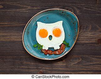 owl-shaped fried eggs with crispy bacon on a plate