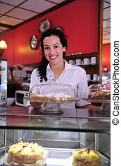 owner of a small business/ cake store/ cafe showing her...