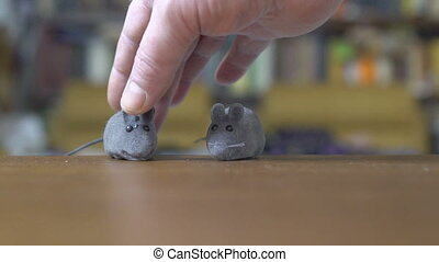 Owner playing with his gray cat. Cute cat catching mouse toy.