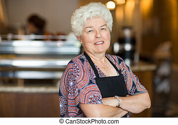 Owner With Arms Crossed Standing In Cafe