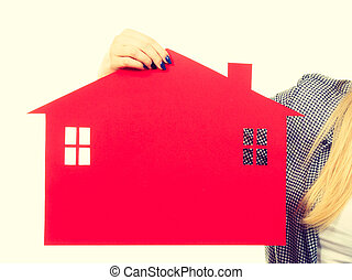 Woman hand holding red paper house