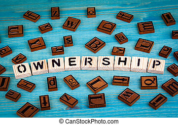 ownership word written on wood block. Wooden alphabet on a blue background