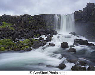 Oxararfoss waterfall in Thingvellir Iceland nature reserve with volcanic rocks and moss, falling from fissure in Mid-Atlantic Ridge, long exposure motion blur
