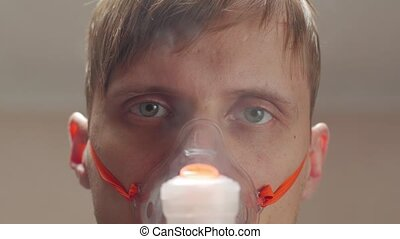Oxygen mask on sick man portrait eyes closeup unshaven messy male interior look into the camera