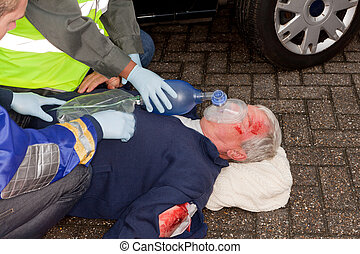 Wounded man after car crash being resuscitated with oxygen mask