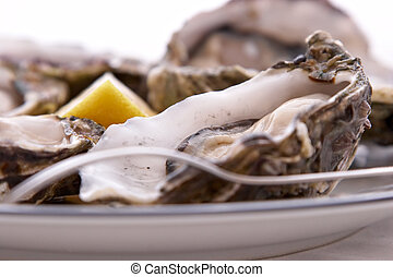 Oysters, Lemon and Fork - Oysters in their shell, with a...