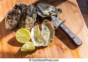 Oysters ready to eat on wooden board