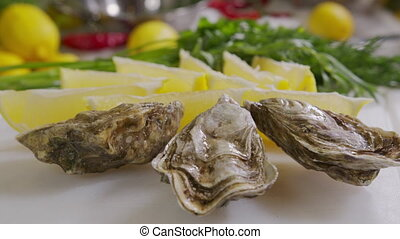 Oysters with lemon closeup. Fresh Oyster on half shell on big plate in restaurant. Served table. 4K UHD video slow motion
