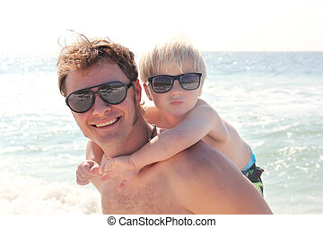 père, fils portant, sur, piggy dos, sur, plage, par, océan