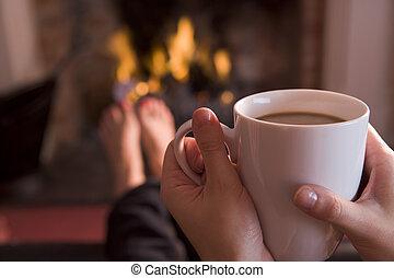 pés, warming, em, um, lareira, com, mãos, segurando café