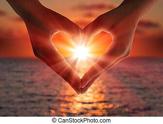 pôr do sol, em, coração, mãos