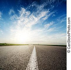 pôr do sol, em, profundo, céu azul, sobre, estrada asfalto