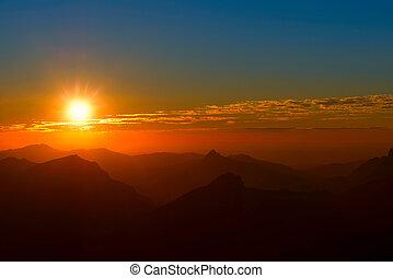 pôr do sol, entre, montanhas, e, nuvens, com, céu vermelho