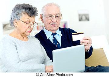 paar, bejaarden, bank, vasthouden, gebruikende laptop, kaart