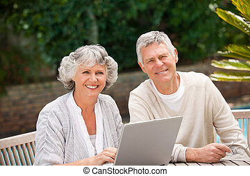 paar, draagbare computer, hun, werkende , gepensioneerd