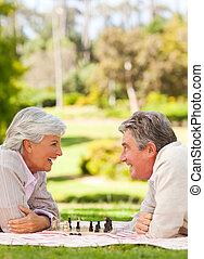 paar, gepensioneerd, spelend schaakspel