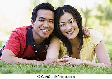 paar, het glimlachen, het liggen, buitenshuis