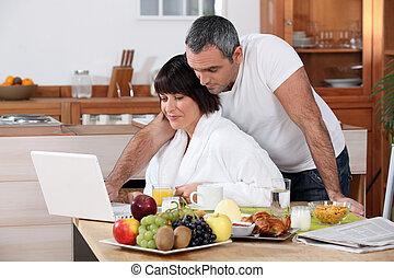 paar, het kijken, hun, gedurende, ontbijt, draagbare computer