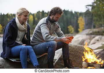 paar, het verwarmen, zich, door, vreugdevuur