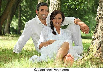 paar, in, witte , zitting op het gras